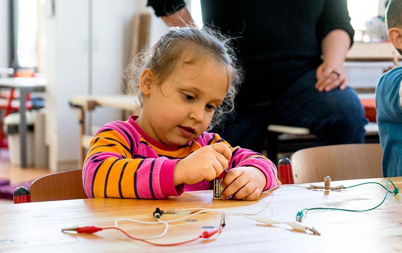 Foto: kleines Mädchen bringt Kabel an Batterie an
